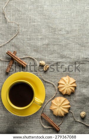 Black coffee in yellow cup with cookies and cinnamon sticks on grey fabric background #279367088
