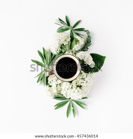 black coffee mug and white hydrangea flowers bouquet on white background. flat lay, top view