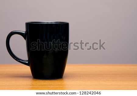 Black coffee mug on wooden table