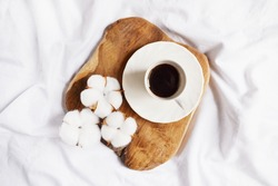 Black coffee on the wooden stab with cotton flowers on the white bedsheet. Cozy home morning. Coffee break. Relaxing atmosphere. Eco life. Autumn style. Hotel room service.