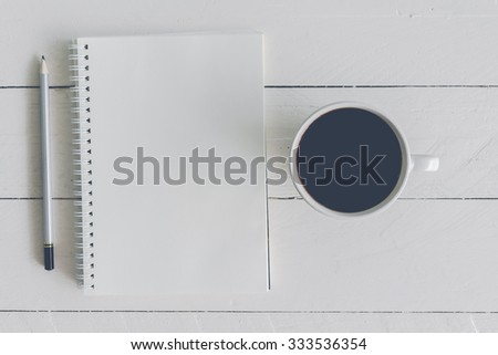 Black coffee with notebook and pencil on wooden background #333536354