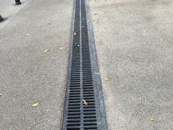 Black color epoxy painted floor drain channel gratings across asphalt road in residential area location for drainage purpose