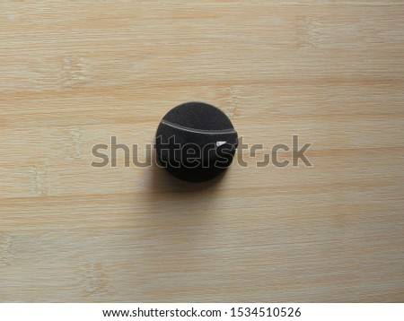 Black color plastic On Off Gas stove knob kept on wooden table