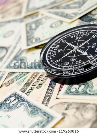 Black compass on dollars.