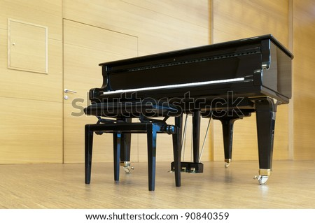 black concert piano is standing on a wooden stage with stool ready for playing