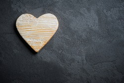 Black concrete background with stone heart, place for chalk text