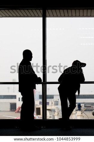 Black contours of passenger against window in the airport lobby. Passengers are waiting for the plane in the terminal. #1044853999