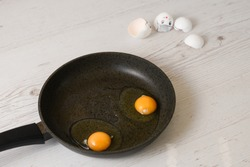 Black cooking pan with raw eggs and white cracked shells with painted confused faces, humanized food