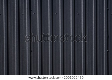 Black corrugated iron sheet used as a facade of a warehouse or factory. Texture of a seamless corrugated zinc sheet metal aluminum facade. Architecture. Metal texture. Foto stock ©