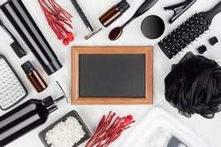 Black cosmetic, accessories for bathing, shower, shave - soap, towel, gel, puff, toothbrush, brush, salt, pumice, red sprig, photo frame on white wood board.