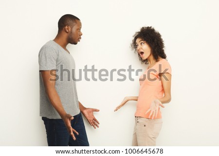 Black couple arguing. Angry african-american men and woman shouting at each other at white studio background, copy space. Break up or divorce, family misunderstanding concept, isolated