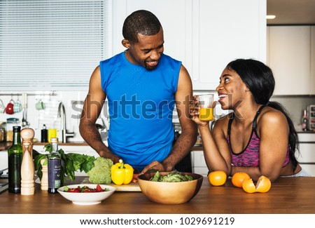 Black couple cooking healthy food in the kitchen