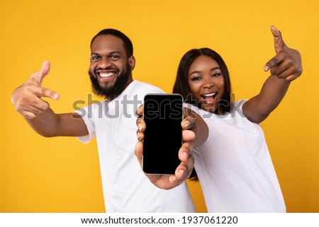 Black couple showing blank empty smartphone screen for mockup