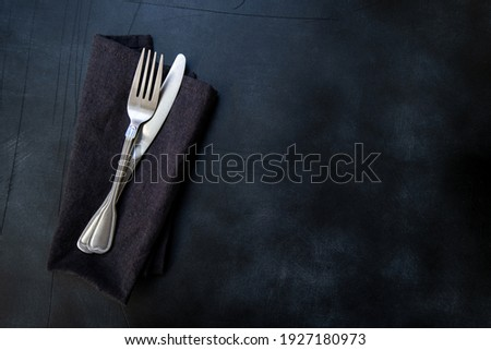 Black craft plate, cutlery and napkin on dark stone table. Top view, copy space, Table setting. background for menu, layout, place for text , recipe background, food flat lay background Photo stock ©