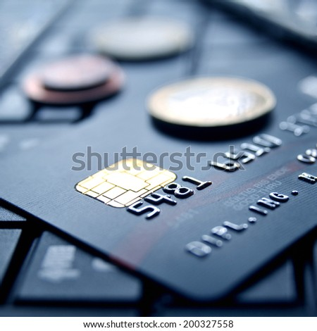 Black credit card on computer keypad with money coins