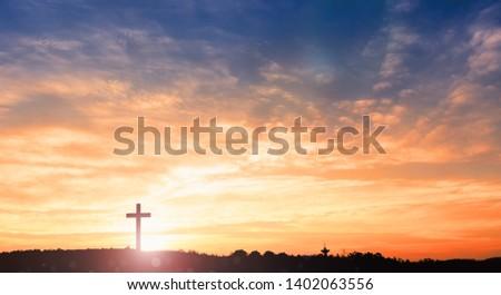black cross religion symbol silhouette in grass over sunset or sunrise sky #1402063556