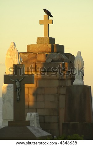 black crow sitting on a tombs cross; woman and jesus statues