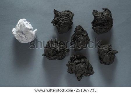 black crumpled paper ball and different white crumpled paper ball on a grey background