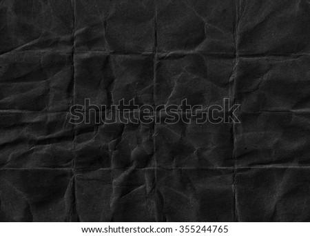 Black crumpled paper. Black background. Grunge paper