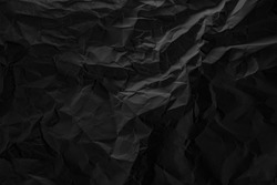 Black crumpled paper texture in low light background