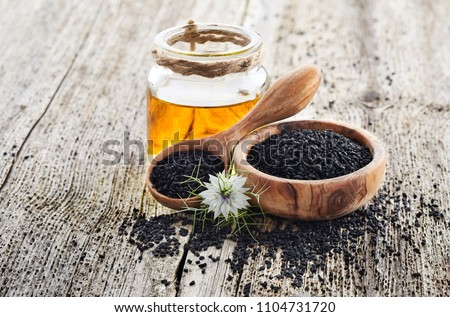 Black cumin oil with flower on wooden background