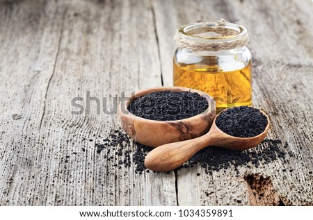 Black cumin oil with seeds on wooden background