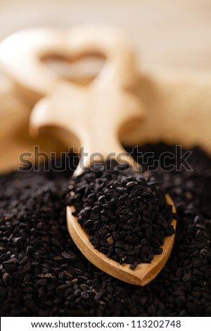 black cumin or caravay or onion seeds in heart shape wooden spoon, shallow dof