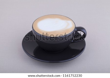 Black cup of cappuccino with foam on textile background