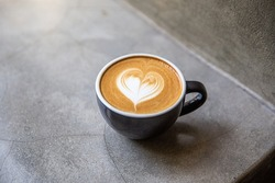 Black cup of cappuccino with latte art of heart shape on saucer on concrete background. Breakfast drink