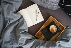 Black cup of coffee on the notebook on the wooden tray and open book with lavender flowers on the bed with grey blanket and black and white pillows. Morning ritual. Breakfast in bed.
