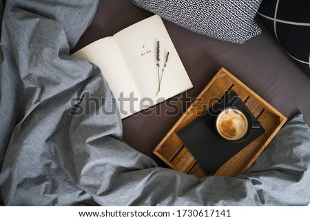 Black cup of coffee on the notebook on the wooden tray and open book with lavender flowers on the bed with grey blanket and black and white pillows. Morning ritual. Breakfast in bed. Stock fotó ©