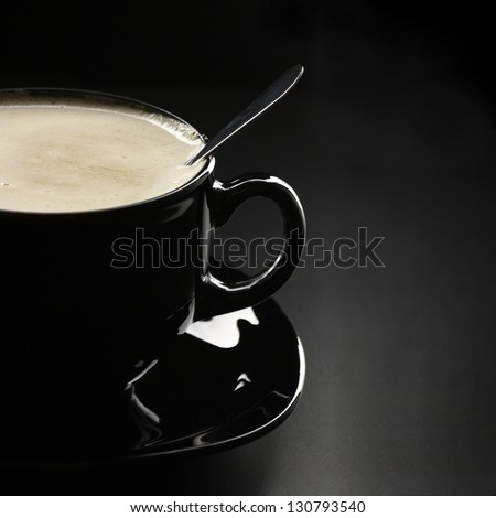 Black cup of coffee with cream and spoon close-up on dark background.
