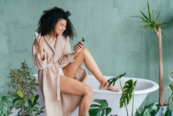 Black curly female wearing bathrobe sits on bathtub choosing between plastic or glass bottle with cosmetic care product. Zero waste concept. Green and conscious lifestyle concept.