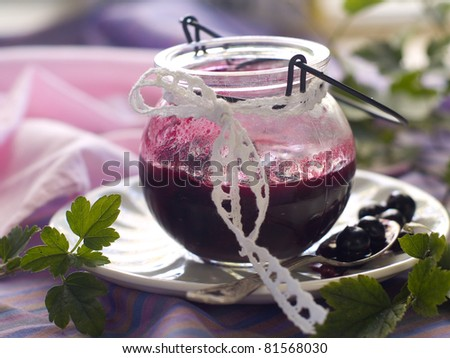Black currant jam in glass jam-jar. Selective focus