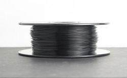 Black 3d printer filament on dark surface, and white background. 1.75