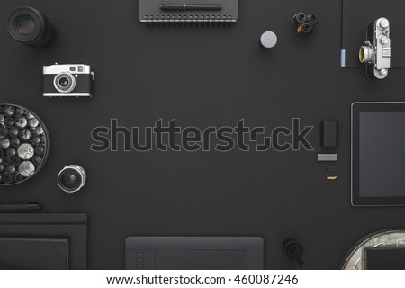 Black desk of photographer. Workspace on black table of a creative designer or photographer with laptop, tablet, cameras other objects of inspiration and copy space. Stylish home studio concept.