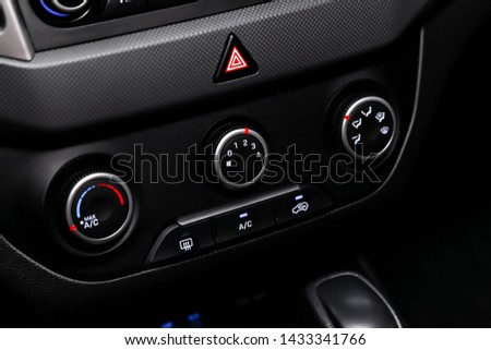 Black detail with the air conditioning button, the dashboard with information about temperature inside a car. modern car interior: parts, buttons, knobs