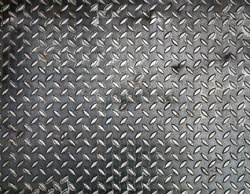 black diamond metal plate background, grunge texture of dark metallic sheet with small oval shape diagonal pattern, embossed surface prevents slipping for stair or walkway and ramp floor
