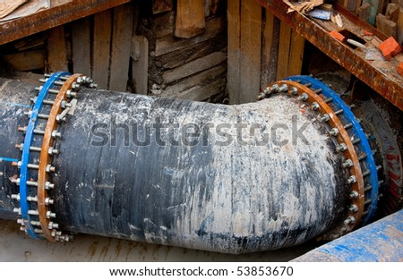 Black dirty sewer pipe with bolted blue rotten clamp