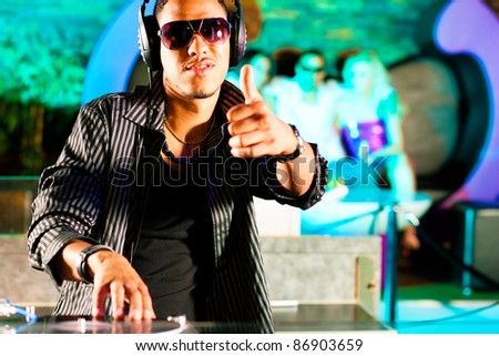 Black DJ in a club at the turntable, in the background the crowd is cheering