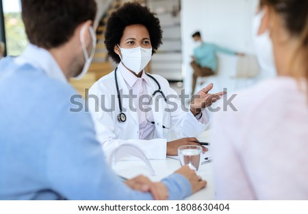 Black doctor wearing protective face mask while talking to her patients during an appointment at clinic.