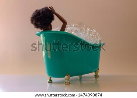 Black doll in miniature bathtub with foam, green plastic, golden feet. Soft background.