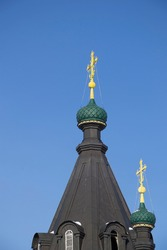 black domes of an Orthodox church with gilded crosses against a blue sky