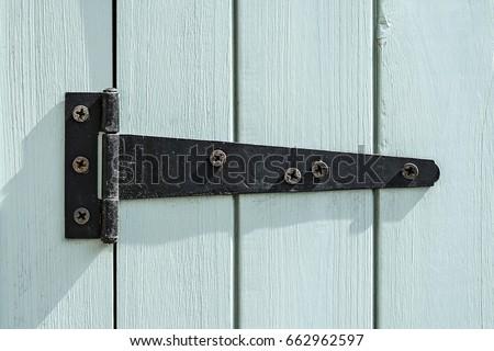 Black door hinge screwed to a bright painted wooden door. #662962597