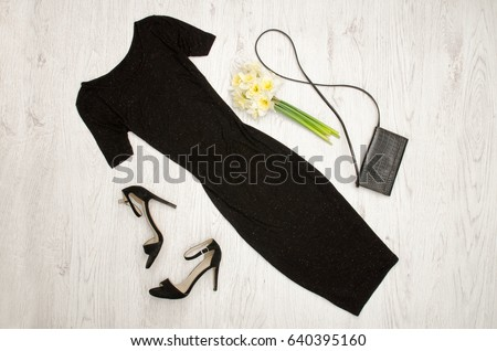 Black dress, shoes, clutch and a bouquet of daffodils. Fashionable concept. Wooden background.
