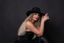 black dressed model girl portrait  with a black hat on black background