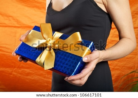 black dressed woman holding a blue gift package