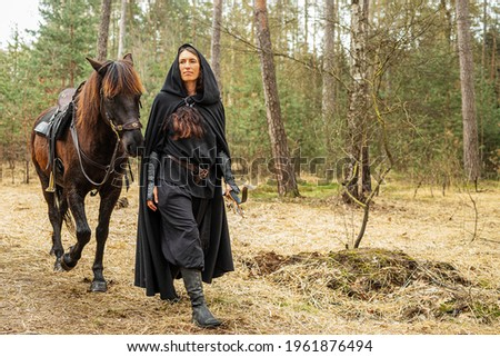 black dressed woman in historical costume with bow and arrow walks through the woods with her horse ストックフォト ©