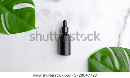 Black dropper bottle on marble background with monstera palm leaf. Blank aromatic oil container design, medical packaging template. Herbal cosmetic concept. Flat lay, top view.