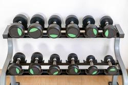 Black dumbbell set. Close up many metal dumbbells arrange on rack in sport fitness center.